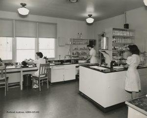 Three women working in Vanport hospital laboratory.