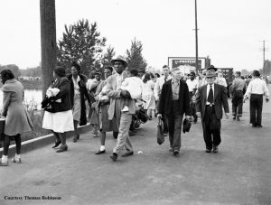 Families leaving the Vanport along Denver Ave. Some people are looking back at their lost homes.  An African American man carries a child.