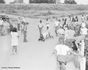 Black and white children on a road (around 20 kids shown) Soap box derby car #15 is in view.