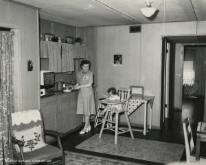 Mother in kitchen next to child in high chair.