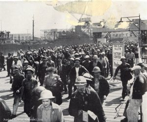 Male and female shipyard workers leaving work site in hard hats (maybe 100 plus people) poor quality damaged edge image