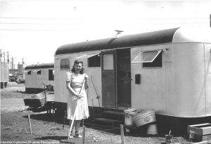 A women resident is sweeping in front of a trailer.