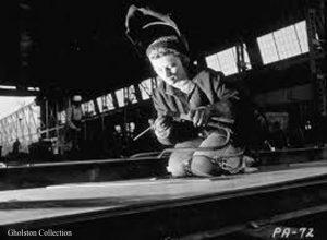 Women welder kneeling on factory floor, not actively welding safety helmet is up. Gholston Collection