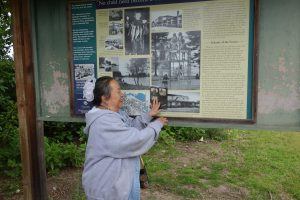 Alma an elder and former Vanport resident is standing in front of an existing historic marker, pointing to a historic B&W image that is significant to her memories.