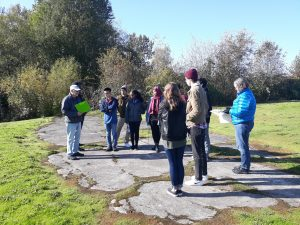 Group touring Vanport site with a guide, they are standing on the foundation of the theater site.