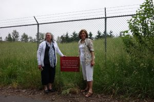 Two women by a fence at what was once the site of their home in Vanport.  They are holding a red sign with the text