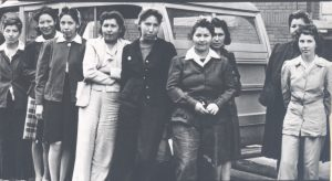 Nine young adult indigenous in pants leaning against a vehicle